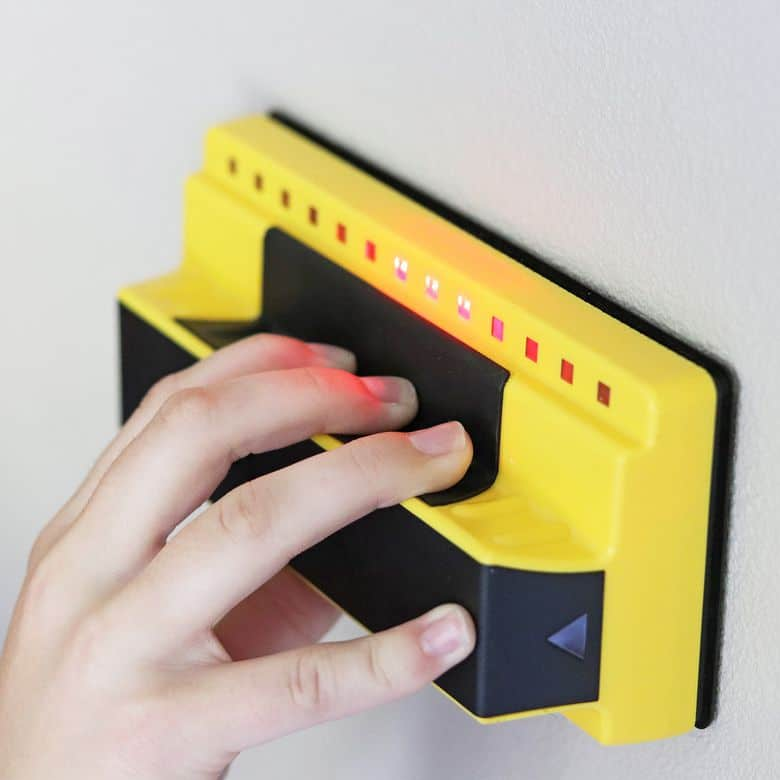 image shows stud finder used for locating holes on walls before mounting TV