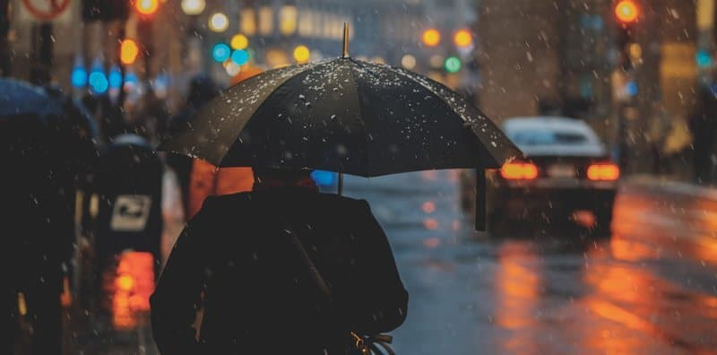 Shows a man in the rain with an umbrella. purpose is to warn against using airpod in heavy rain because it is not waterproof