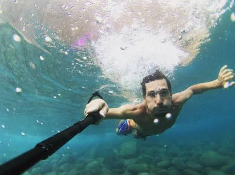 Shows taking selfie in the water with iPhone XR